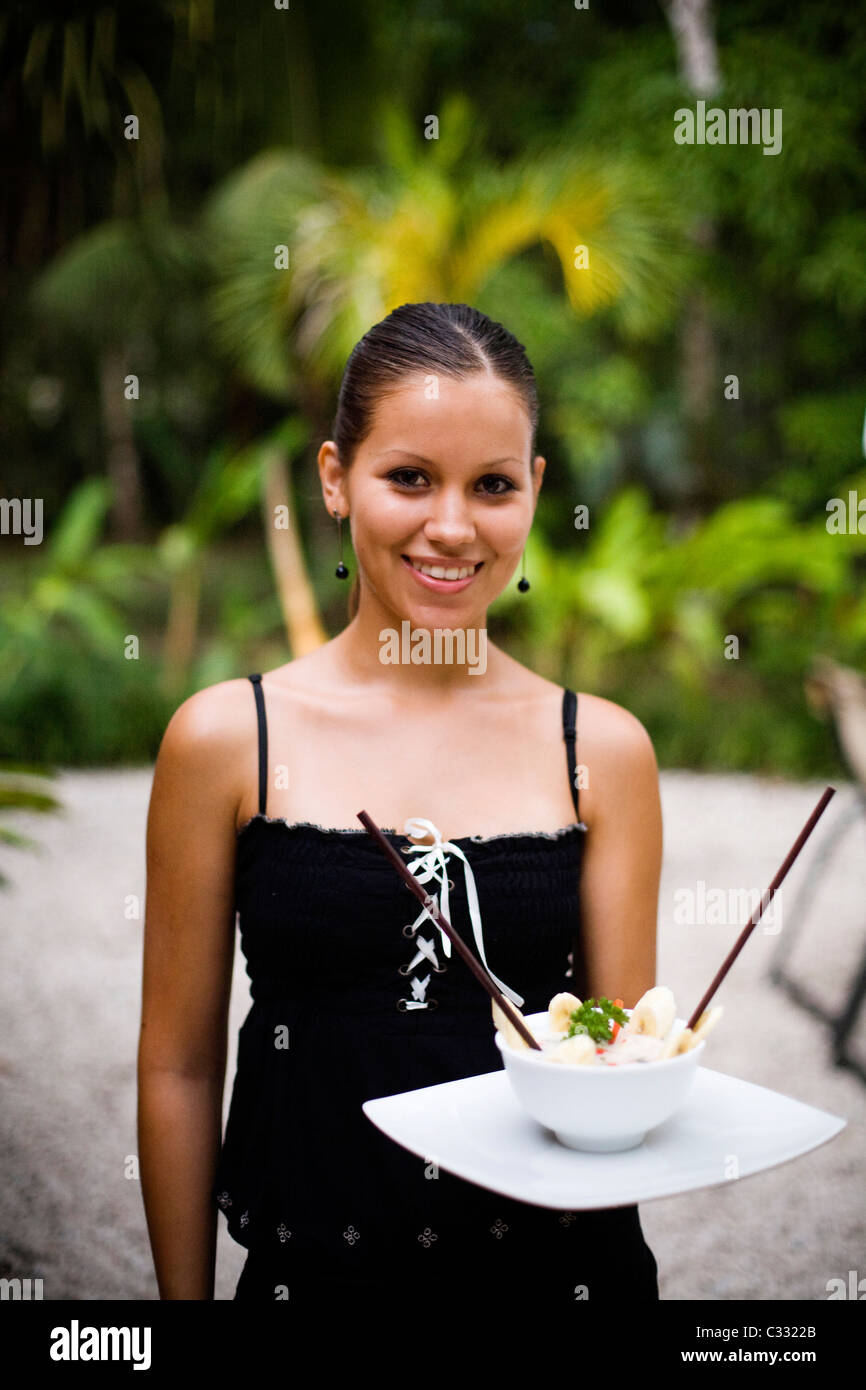 A portrait of a woman holding a bowl of ceviche. - Stock Image