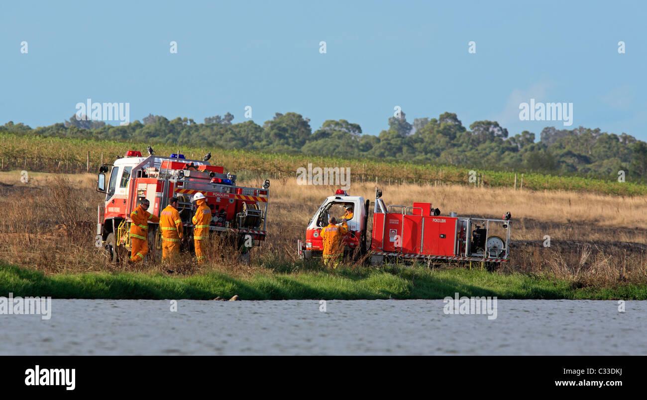 volunteer-firefighters-at-their-fire-trucks-after-attending-a-grass-C33DKJ.jpg