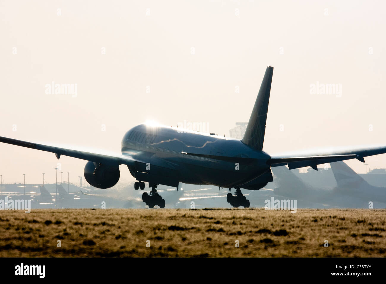 Commercial airliner landing at London Heathrow with condensation trails forming over the wings. Stock Photo