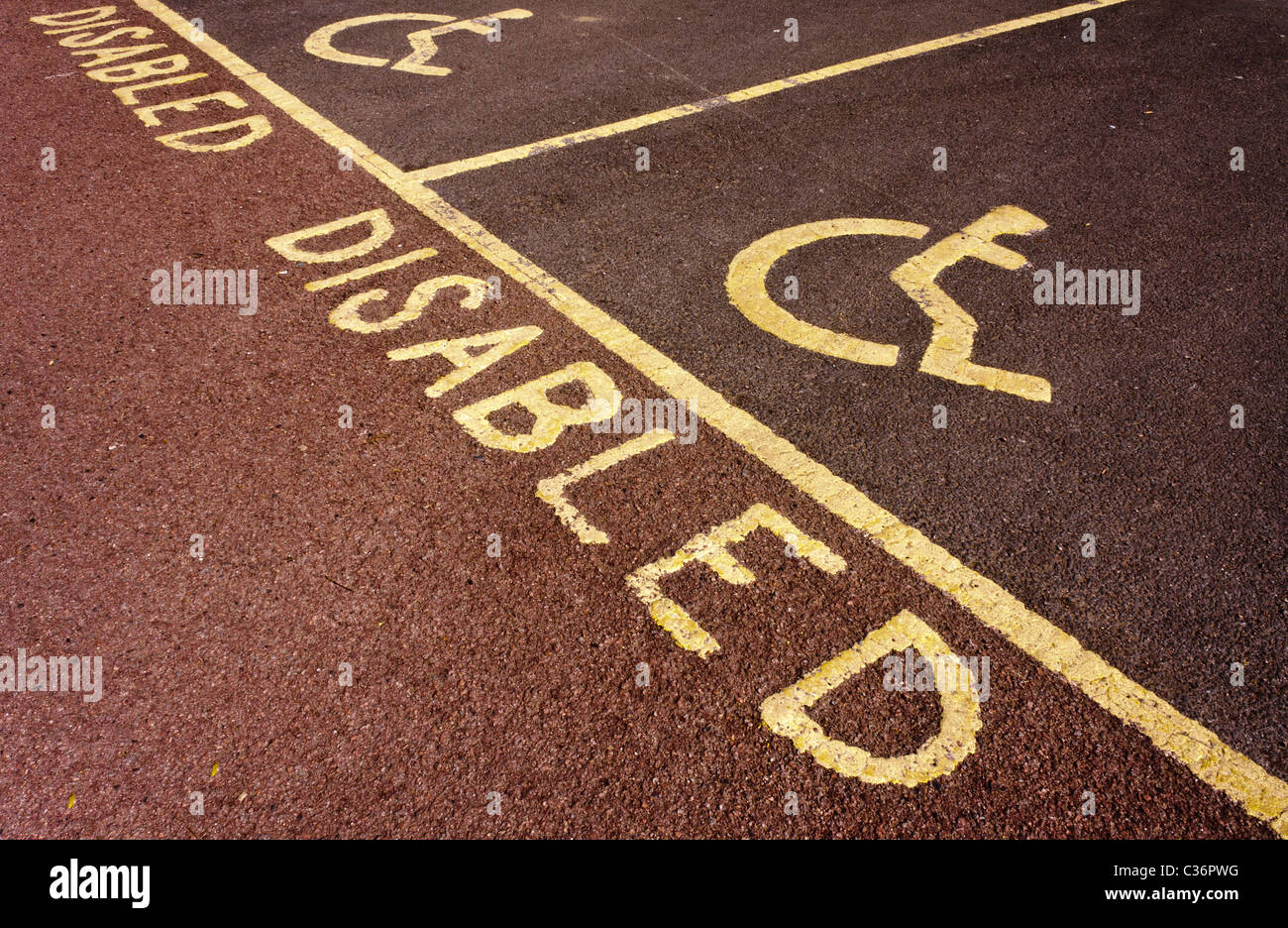 Disabled parking bay with wheelchair user icon, painted yellow on red tarmac. Stock Photo