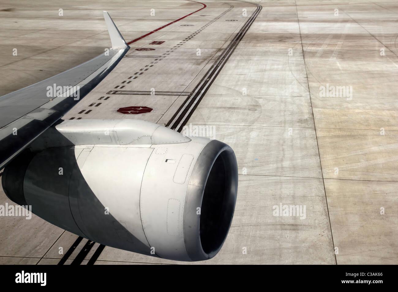 airplane wing aircraft turbine landing on runway road - Stock Image