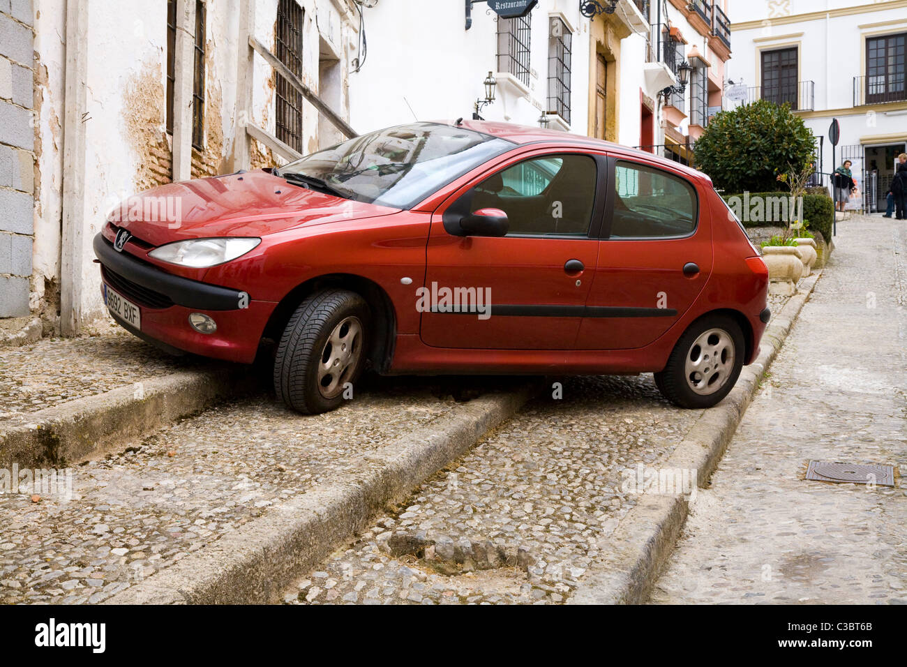 A Peugeot 206 car parked on the pavement in typical traditional ...