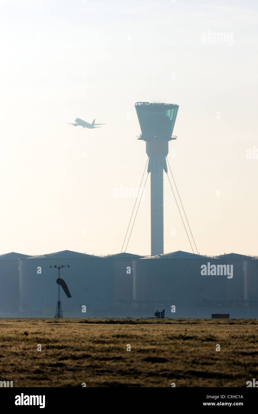 Comercial airliner taking off and London's Heathrow control tower. Stock Photo