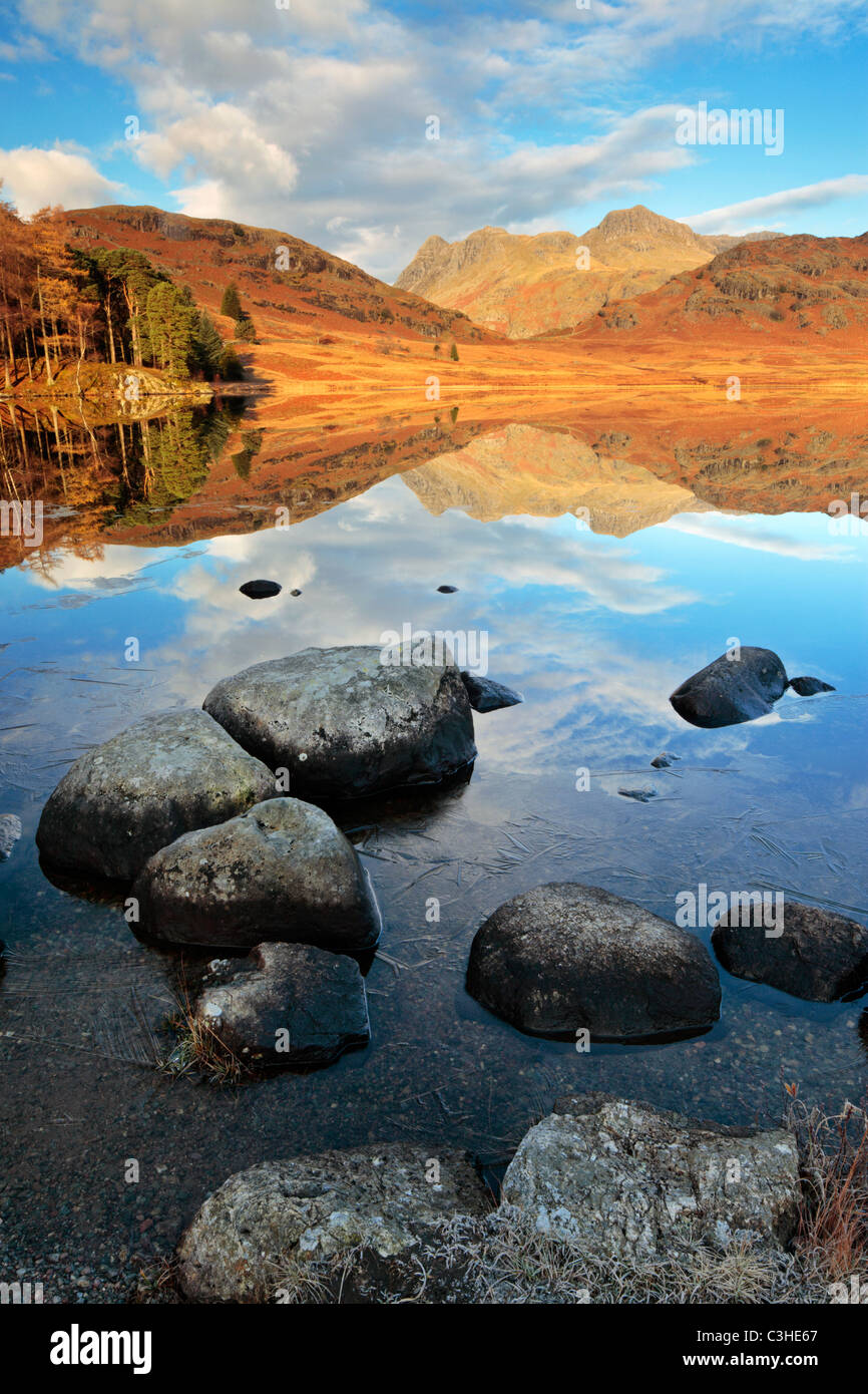 Late Autumn ice lines the rocky shores of Blea Tarn in front of a perfect reflection of Side Pike and the Langdales - Stock Image