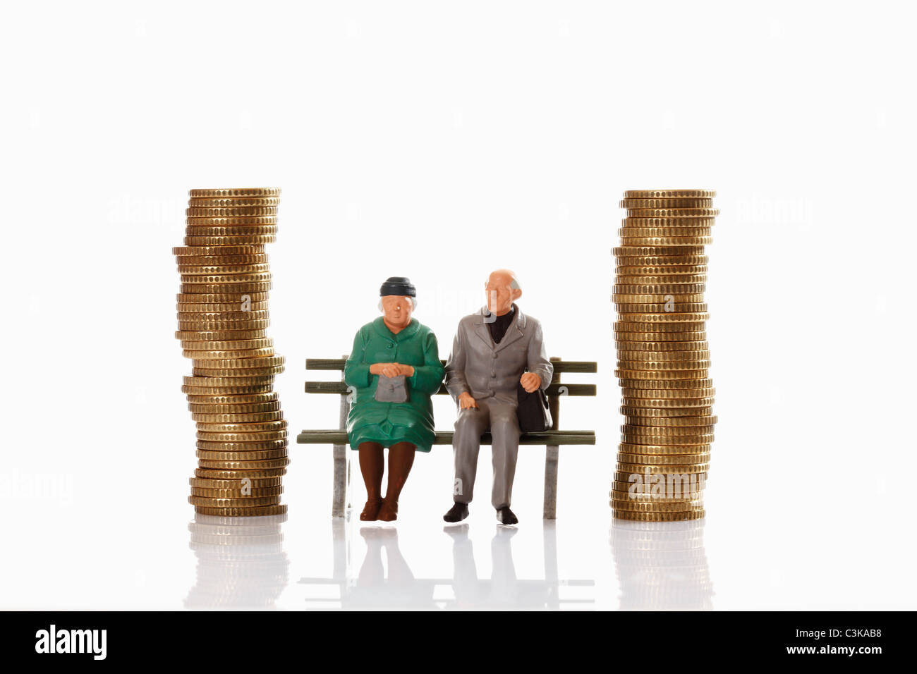 Figurines of old age pensioner sitting on bench between coin stacks - Stock Image