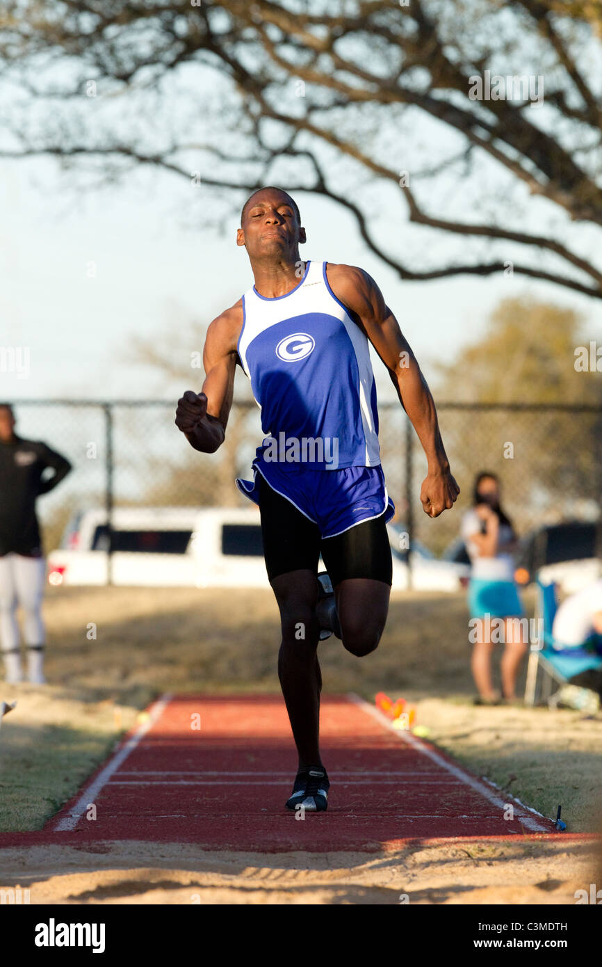African-American male athlete approaches takeoff in the long jump at high school track meet in San Antonio Texas - Stock Image
