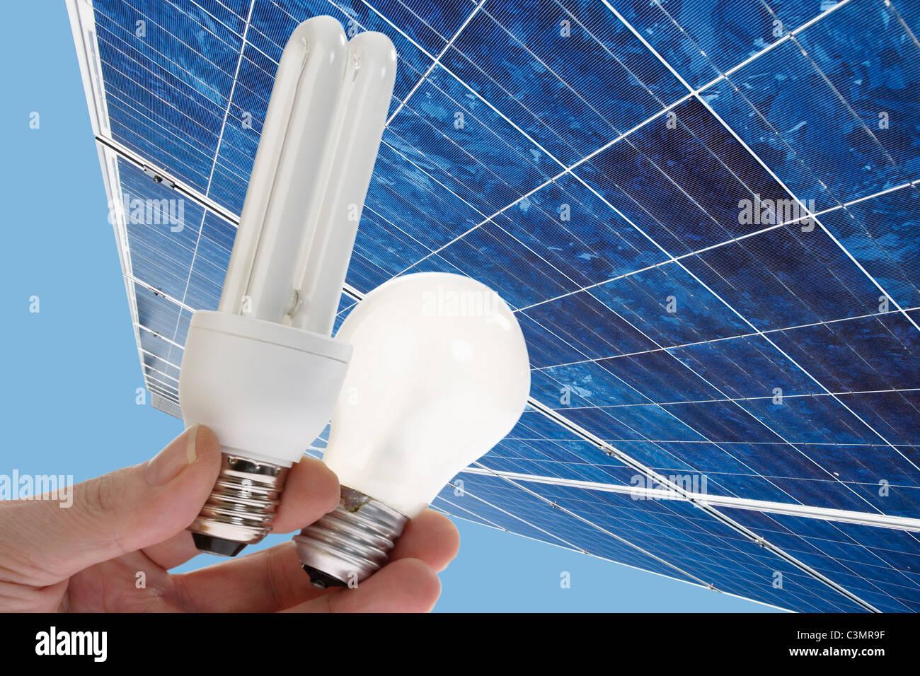 Human hand holding energy saving light, bulb against  solar panel, close up. - Stock Image