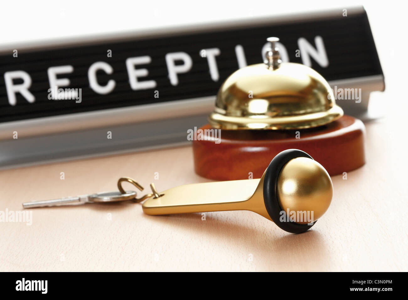 Reception sign with service bell and hotel key on desk - Stock Image
