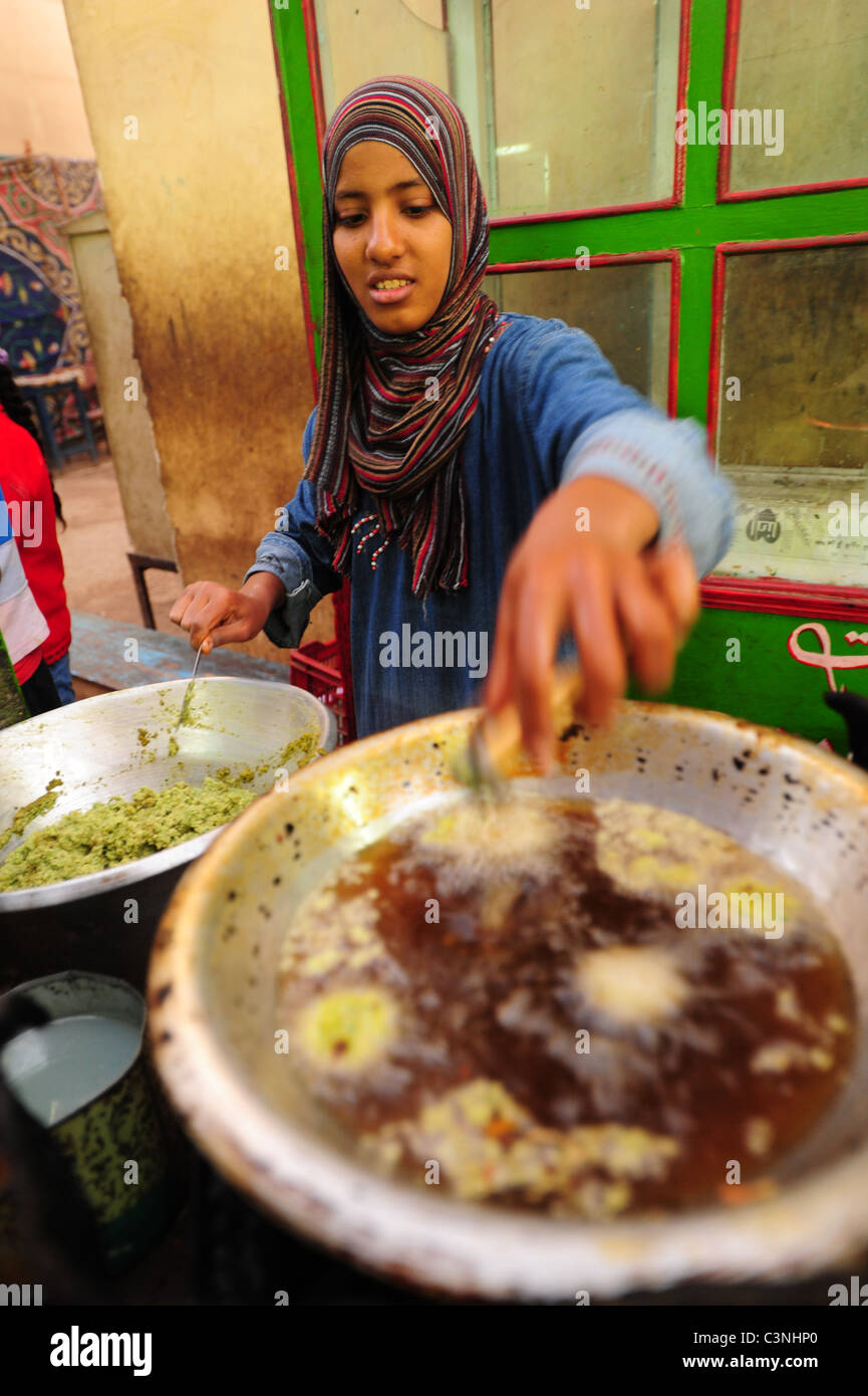 Africa Middle East Egypt Egyptian Luxor El Souk Market alley shopping and food - a young woman is frying falafel Stock Photo