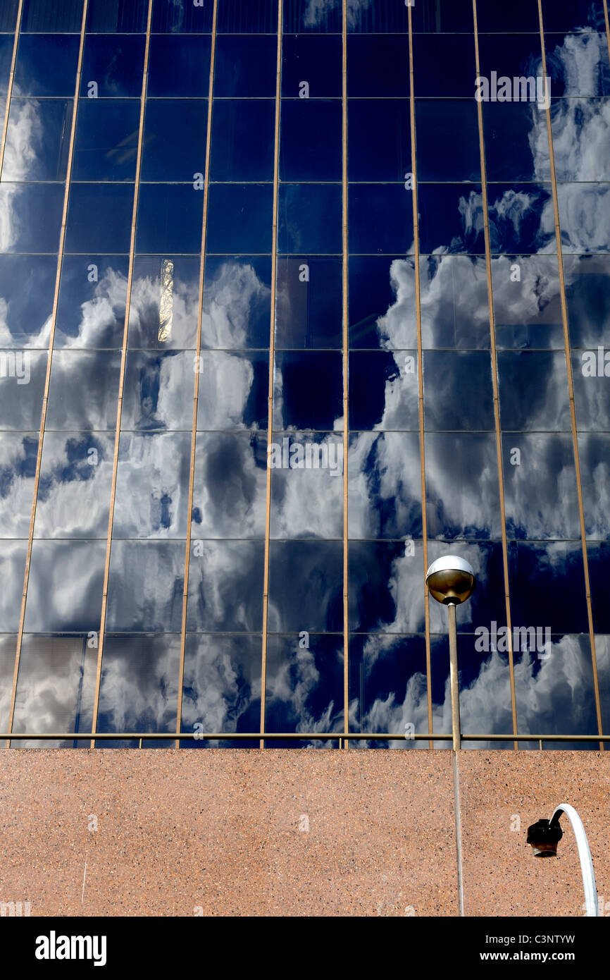 clouds in deep blue sky reflected in windows of tall building - Stock Image