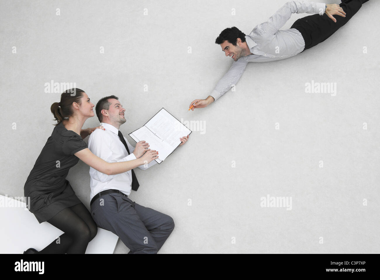 Three business people, businessman signing contract, elevated view - Stock Image