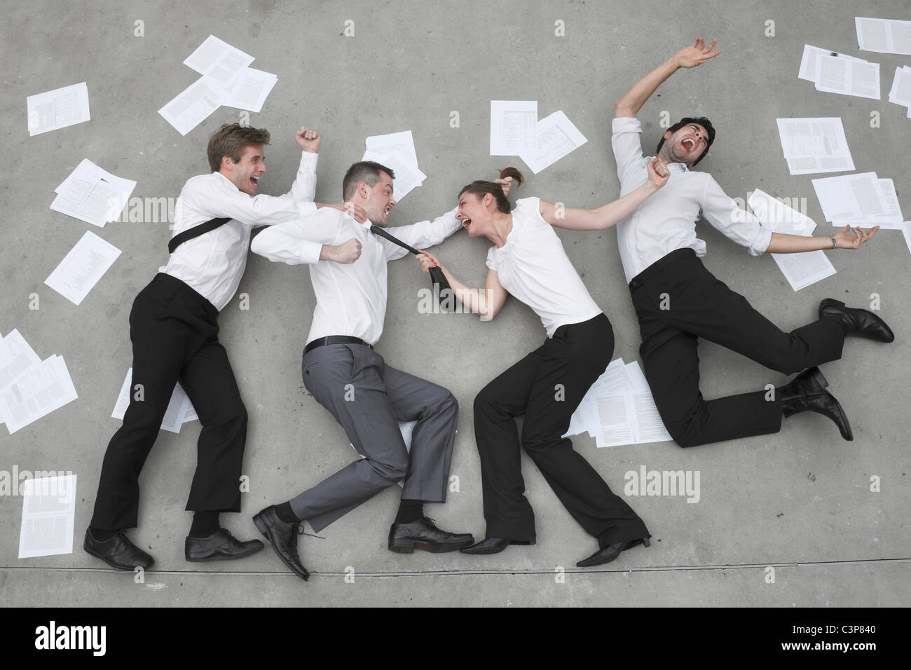 Three business people in a quarrel, woman pulling man's ties, elevated view - Stock Image