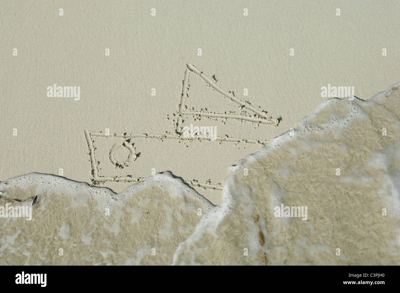 Ship drawn in sand on beach by sea. - Stock Image