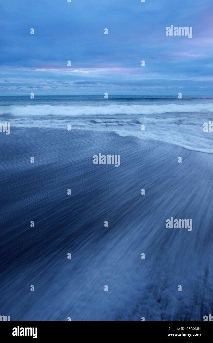 USA, Washington State, Olympic National Park, View of blurred waves on dark sandy beach - Stock Image