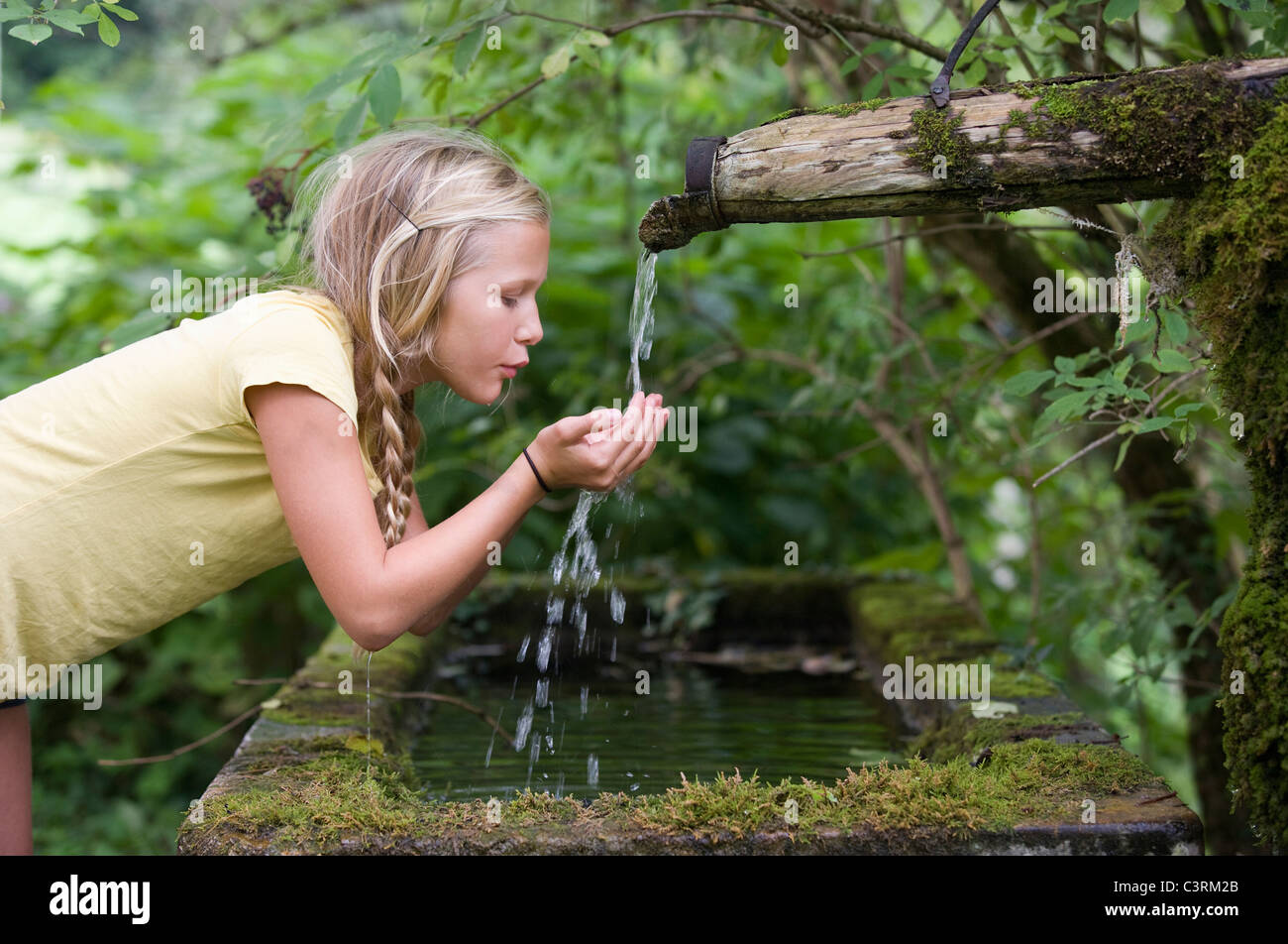 Austria, Mondsee, Girl (12-13 Years) drinking water from water spout - Stock Image
