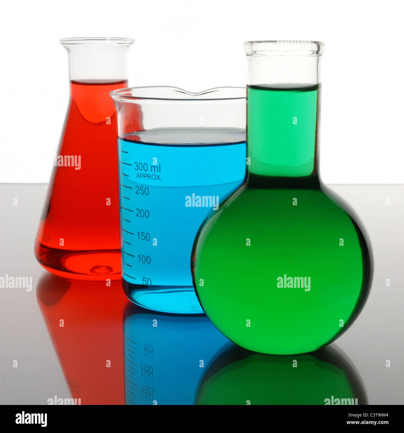 laboratory beaker and flasks containing red, blue, green liquids - Stock Image