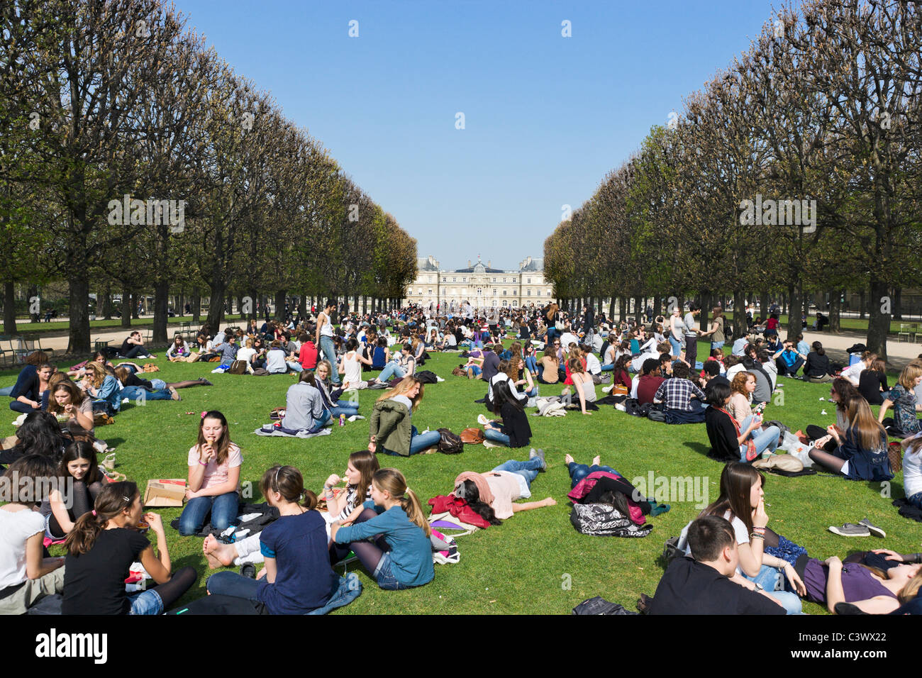 Students having lunch on lawns in front of Palais du Luxembourg in  early spring sunshine, Jardin du Luxembourg, - Stock Image