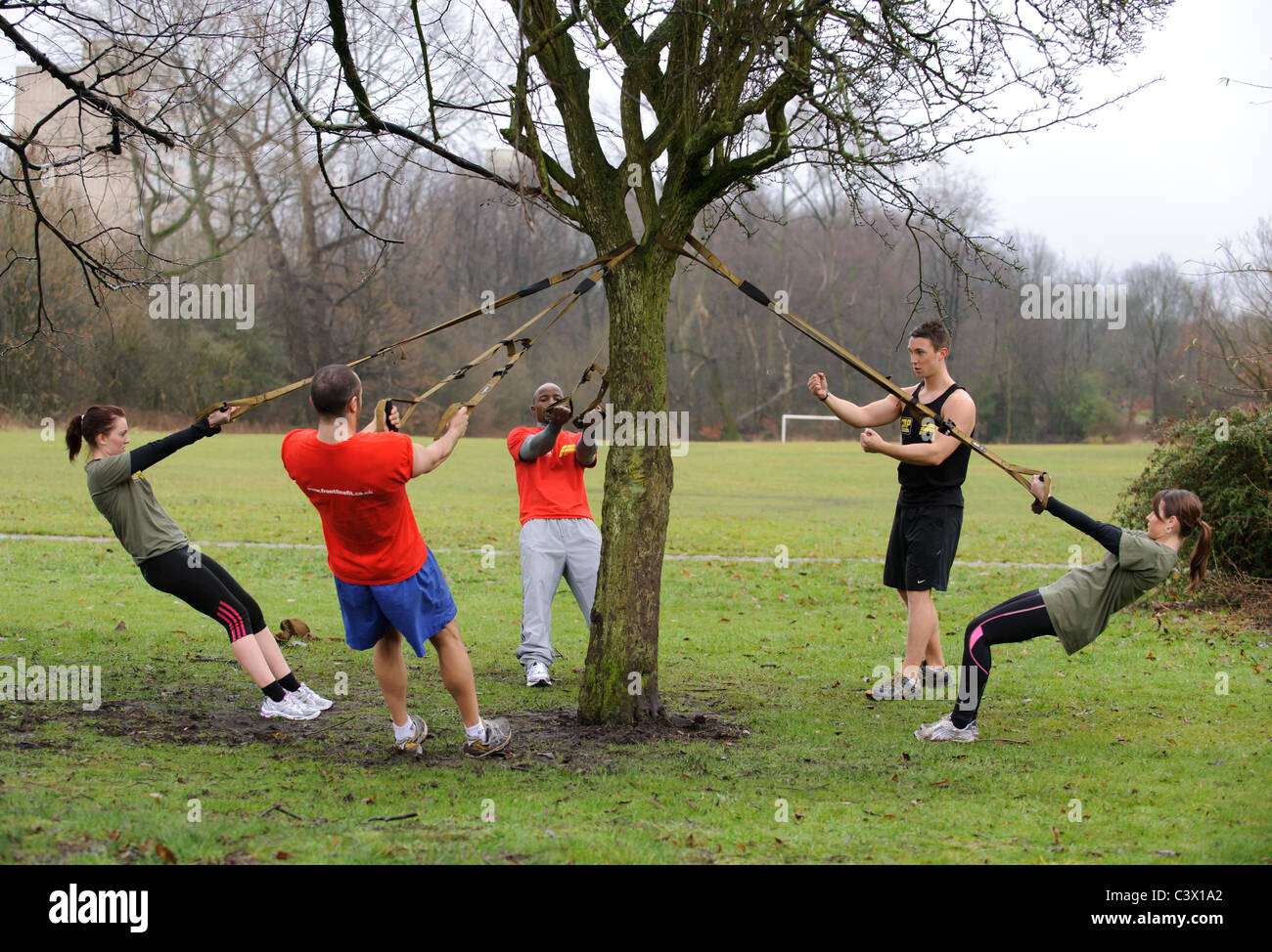 men and women working out at fitness boot camp with instructor - Stock Image
