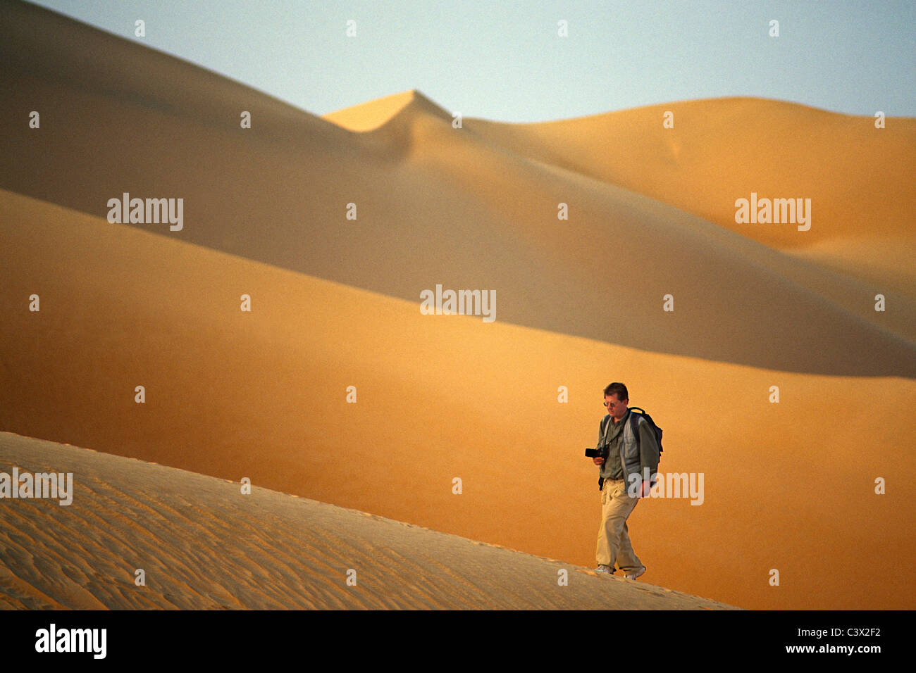 Algeria, Djanet, Sahara Desert, Photographer, man, walking on sand dune. - Stock Image