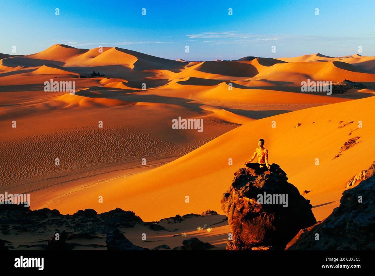 Algeria, Djanet. Sand dunes and rocks. Woman meditating. Sahara Desert. - Stock Image
