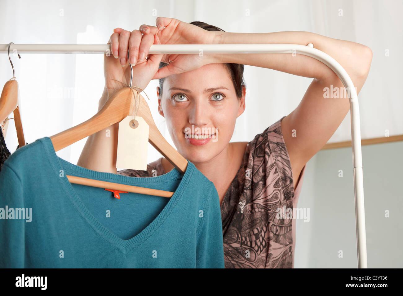 woman holding clothing rail - Stock Image