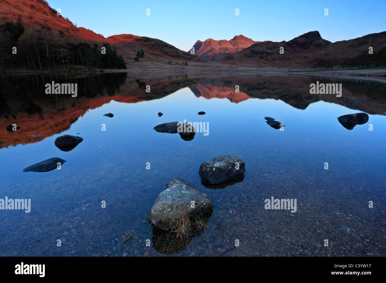 Late autumn light on the icy edges of a calm Blea Tarn in the Lake District of England - Stock Image