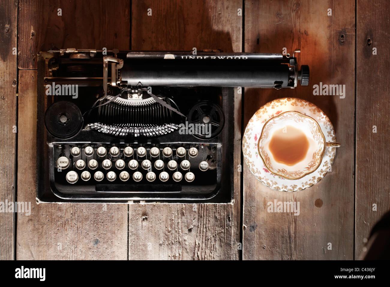 Vintage Underwood 3-bank portable typewriter and  vintage tea cup & saucer Stock Photo