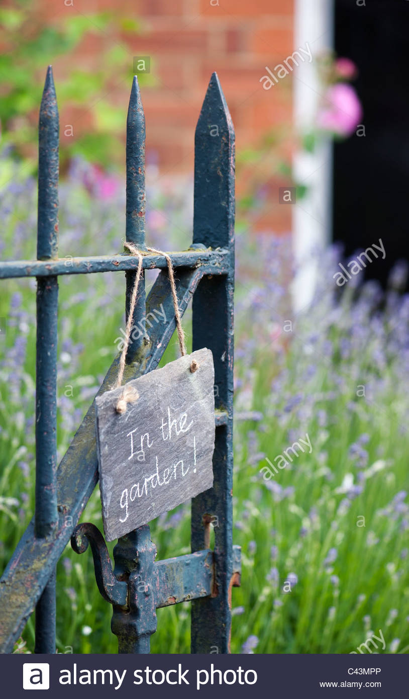 'In the garden', written in chalk on slate, hanging on a the front gate of an english garden. UK - Stock Image