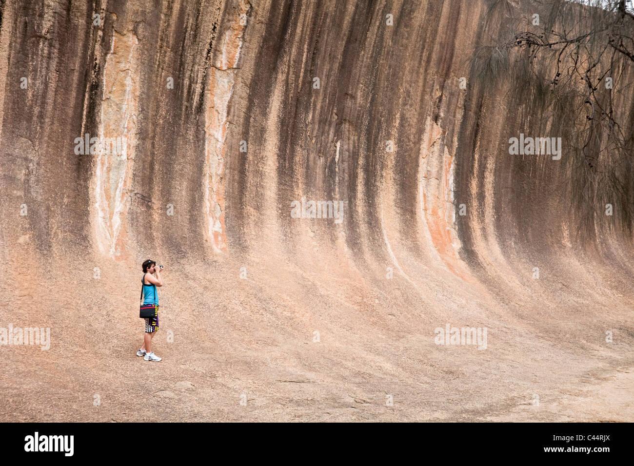 Tourist at Wave Rock - a natural rock formation near Hyden, Western Australia, Australia - Stock Image