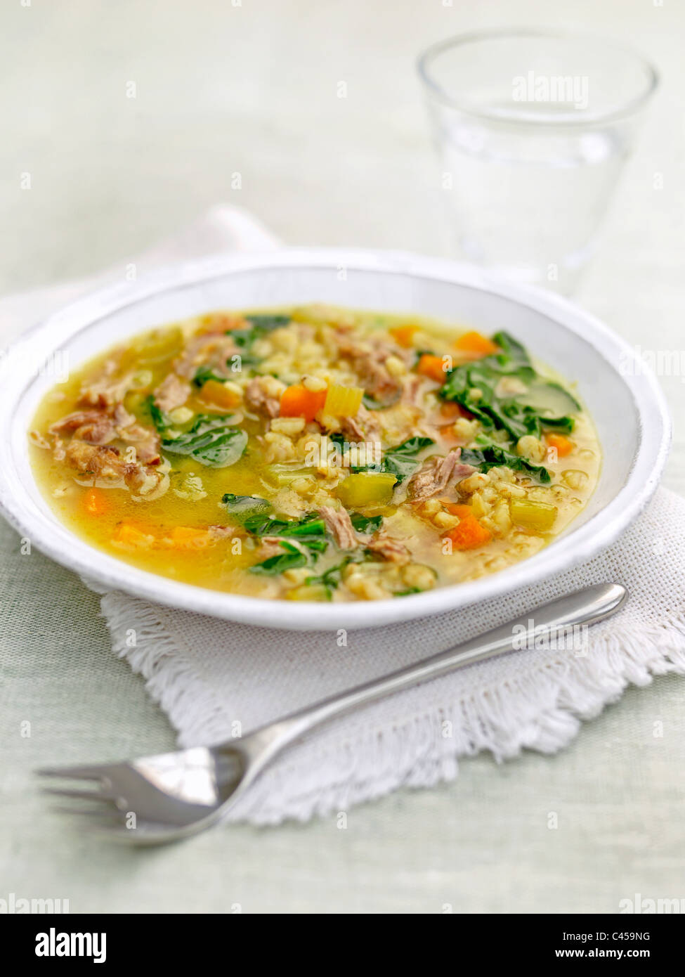 Plate of lamb with barley and spinach stew, close-up - Stock Image