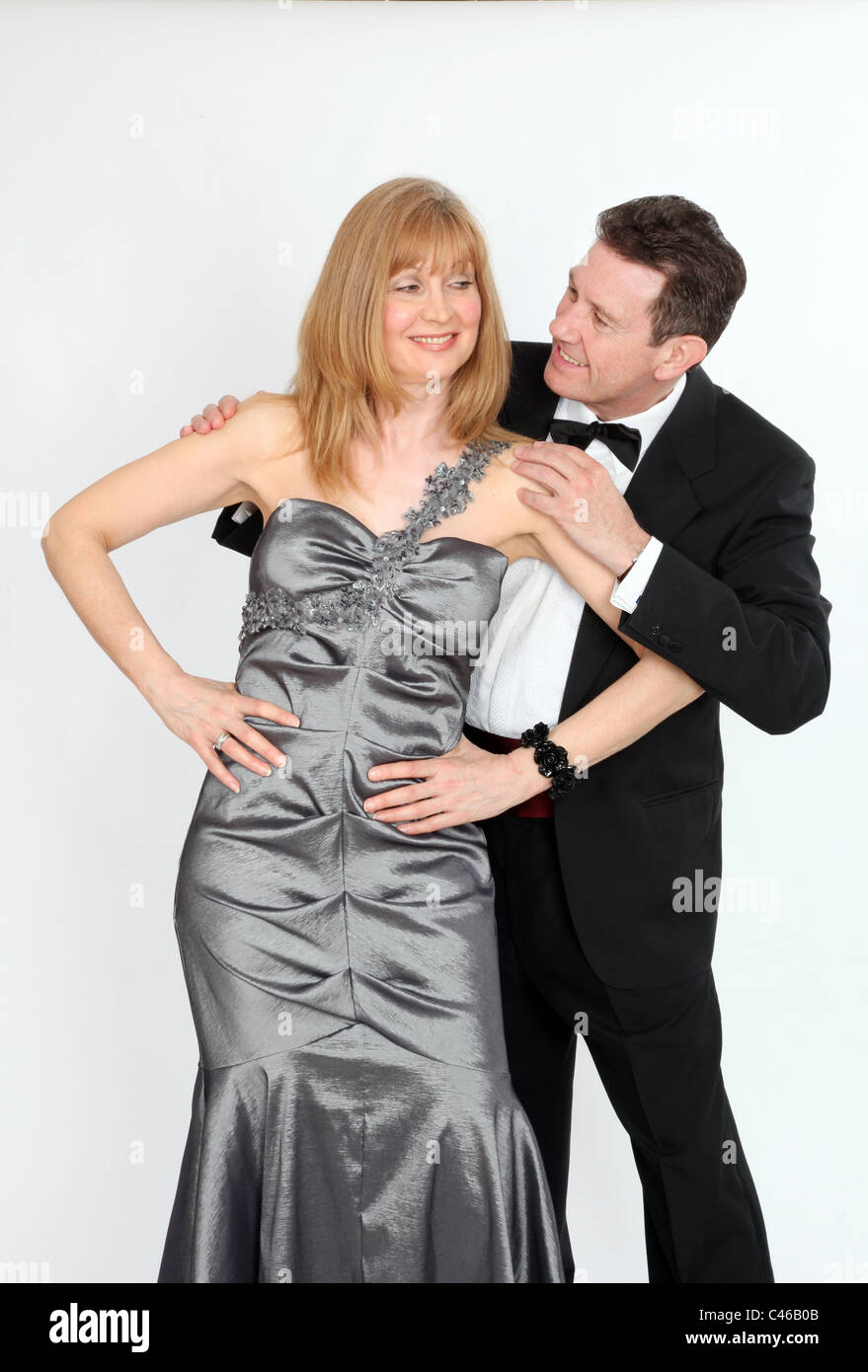 Woman wearing long formal dress hands on hips, man hands on her shoulders, both looking at each other with cheeky - Stock Image