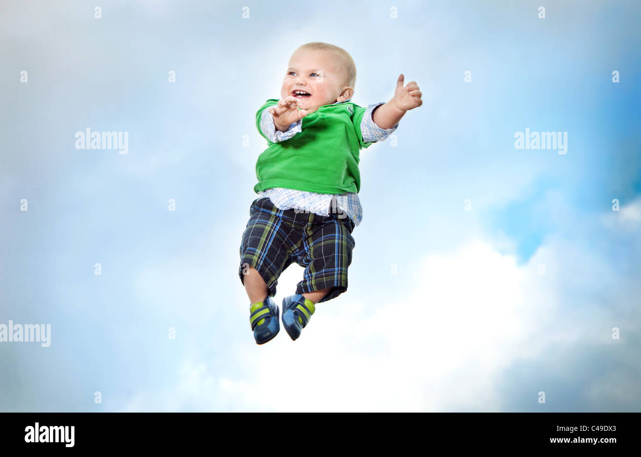 A baby boy in trendy clothing flying in mid-air against a blue sky. - Stock Image