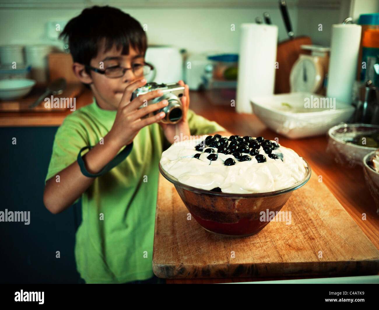 Boy takes picture of homemade trifle. - Stock Image