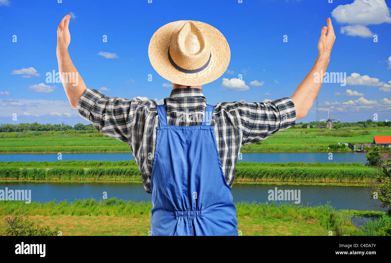 A farmer gesturing with raised hands with field in the background - Stock Image