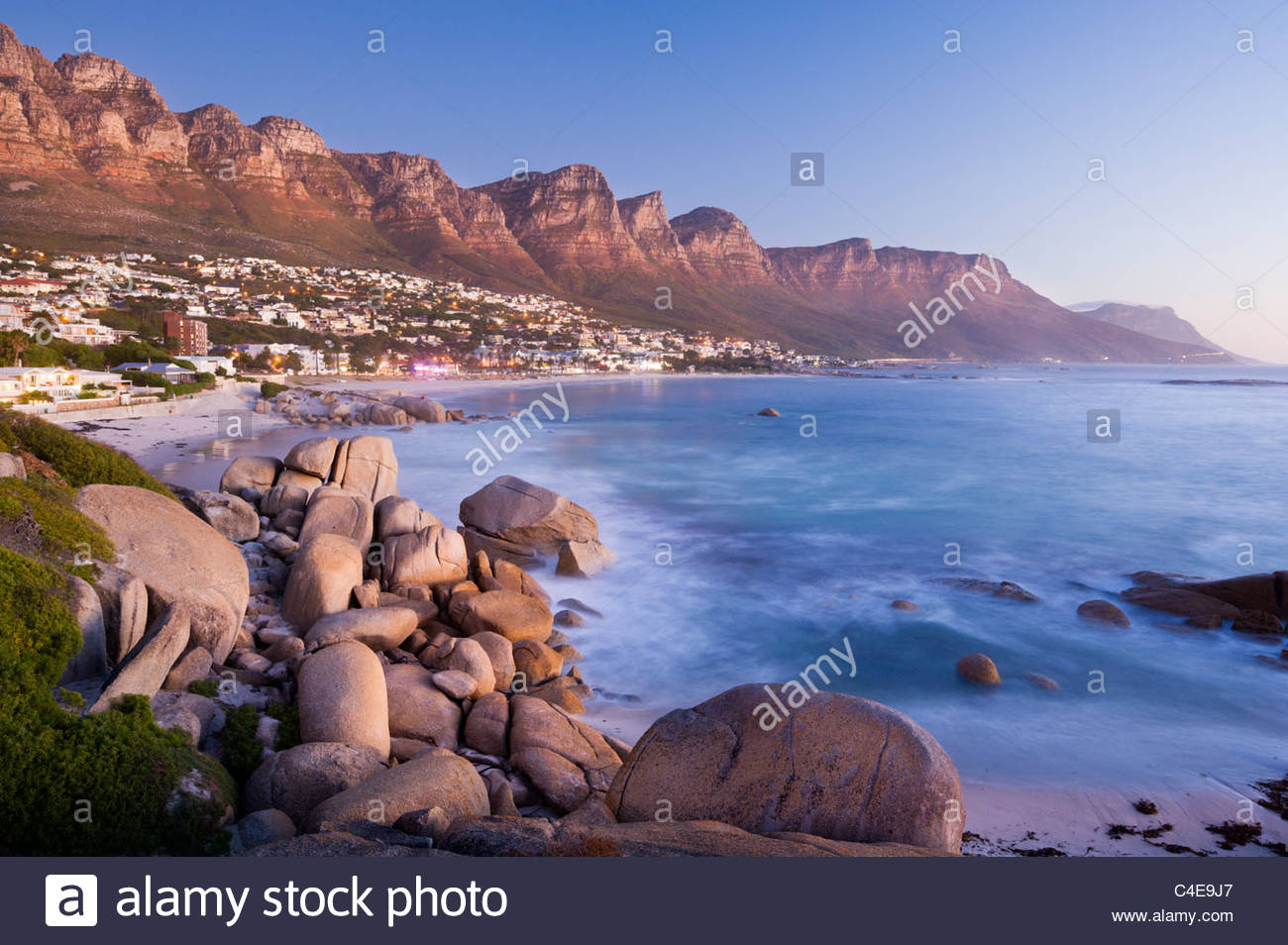 The Twelve Apostles loom over Camps Bay, near Cape Town, South Africa. - Stock Image