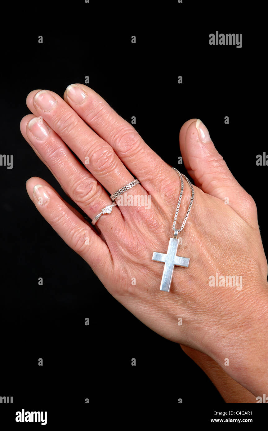Woman is praying holding her cross. On black clean background Stock ...