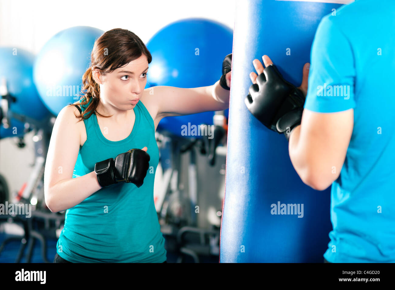 Woman Boxer hitting the sandbag, her trainer is assisting - Stock Image