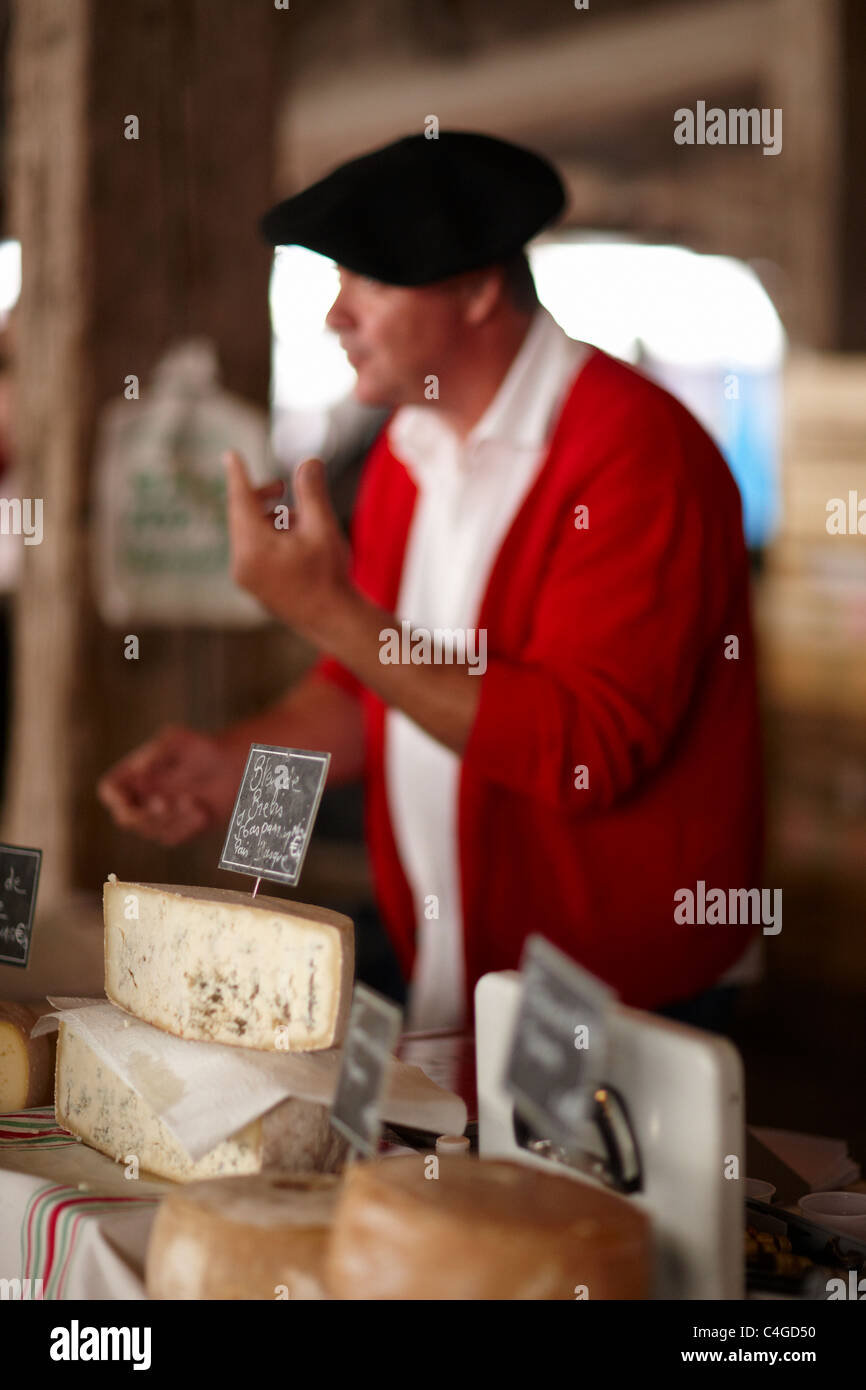 a man selling cheese in the market in Revel, Languedoc, Midi-Pyrenees, France - Stock Image
