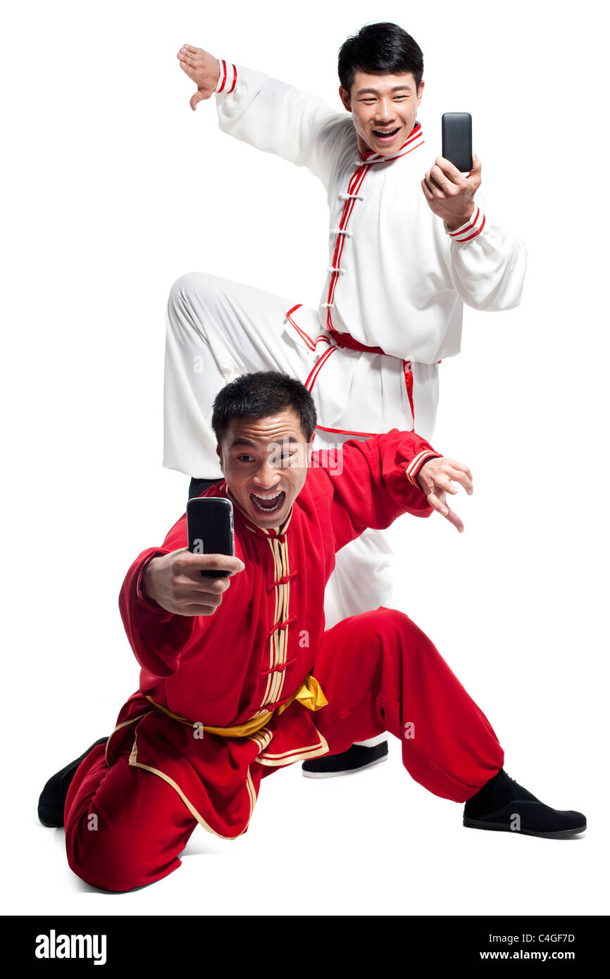 Men Doing Martial Arts and Looking at Mobile Phone - Stock Image