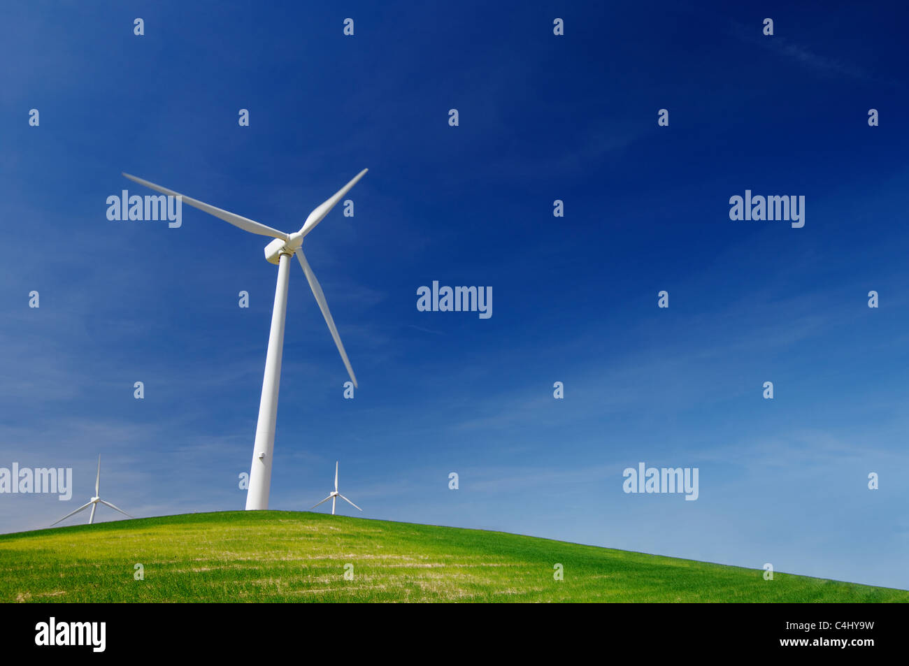 windmills on a green hill with blue sky - Stock Image