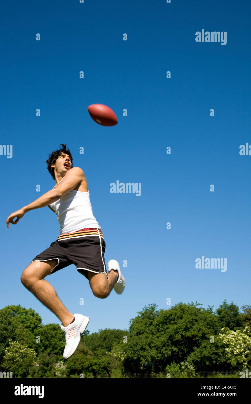 Man jumping playing with oval ball in park - Stock Image