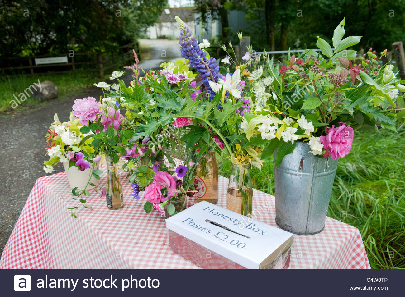 Posies of colourful cut flowers for sale on a roadside table with honesty  box - Stock Image