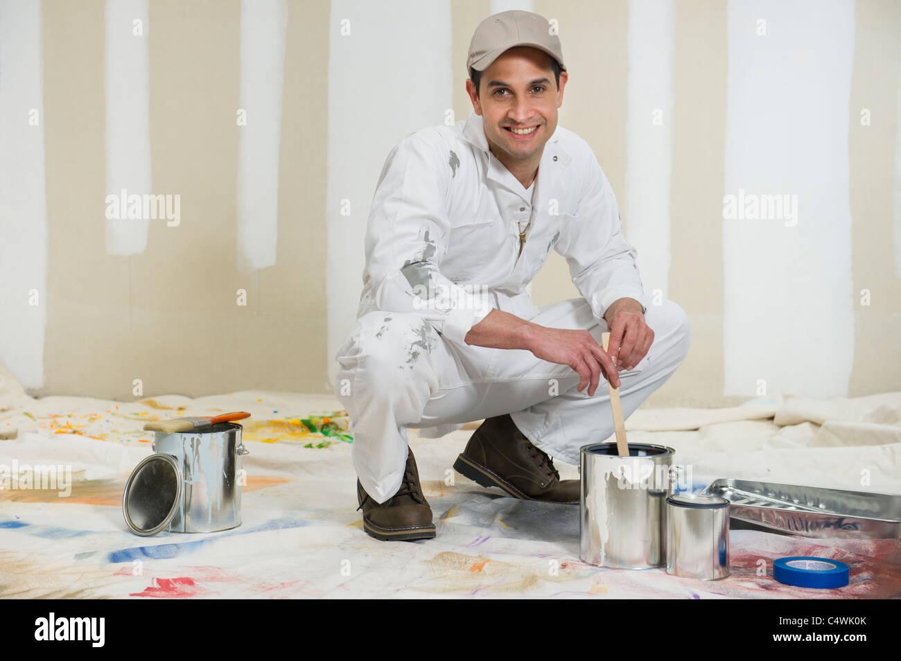 USA,New Jersey,Jersey City,house painter stirring paint - Stock Image
