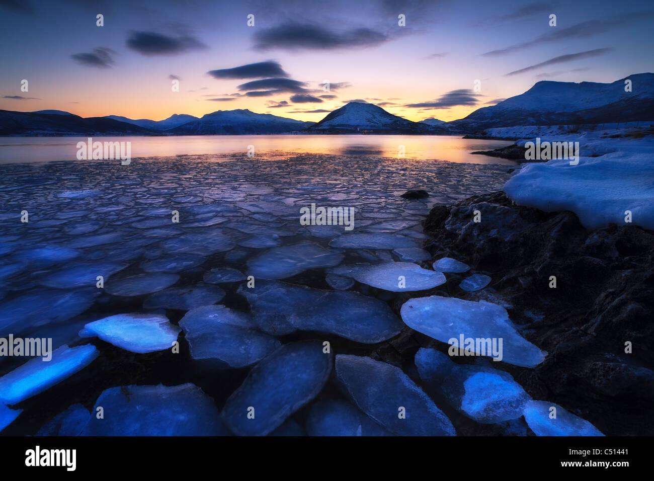 Ice flakes drifting against the sunset in Tjeldsundet strait, Troms County, Norway. - Stock Image
