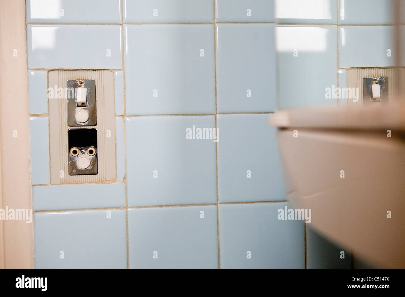 Ight switch and electrical outlet on tiled wall Stock Photo ...