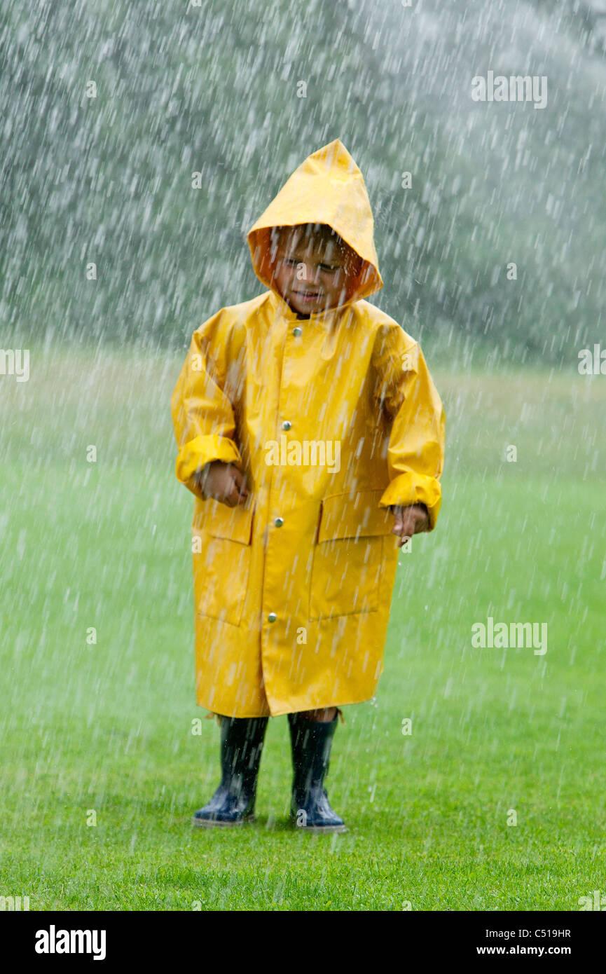 portrait of young boy wearing yellow raincoat - Stock Image