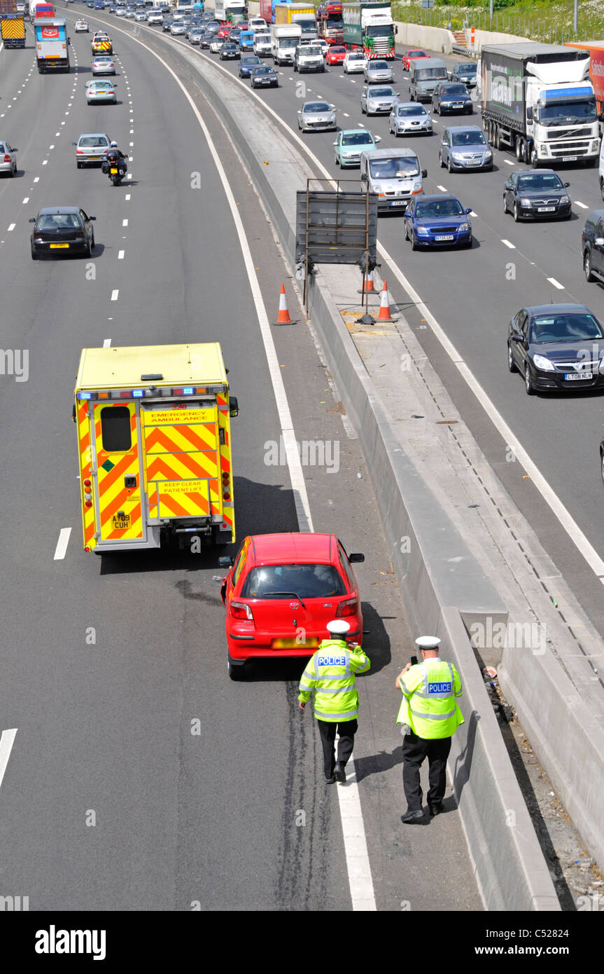 Motorway traffic police inspecting car involved in road accident includes stationary ambulance (note lorry skid - Stock Image