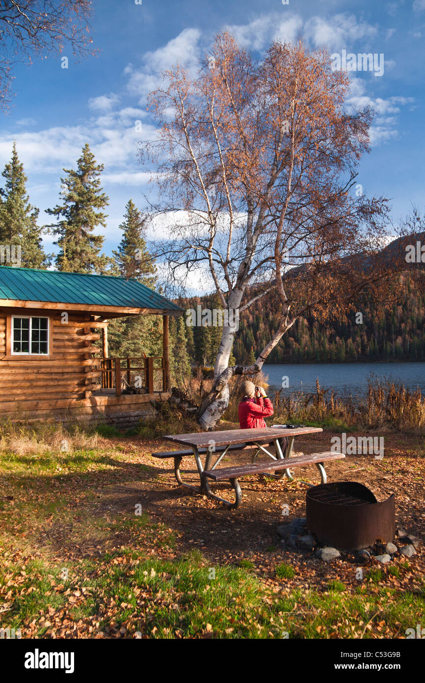 Woman enjoys looking at views through binoculars while at a picnic table, Byers Lake Public Use Cabin, Denali State - Stock Image