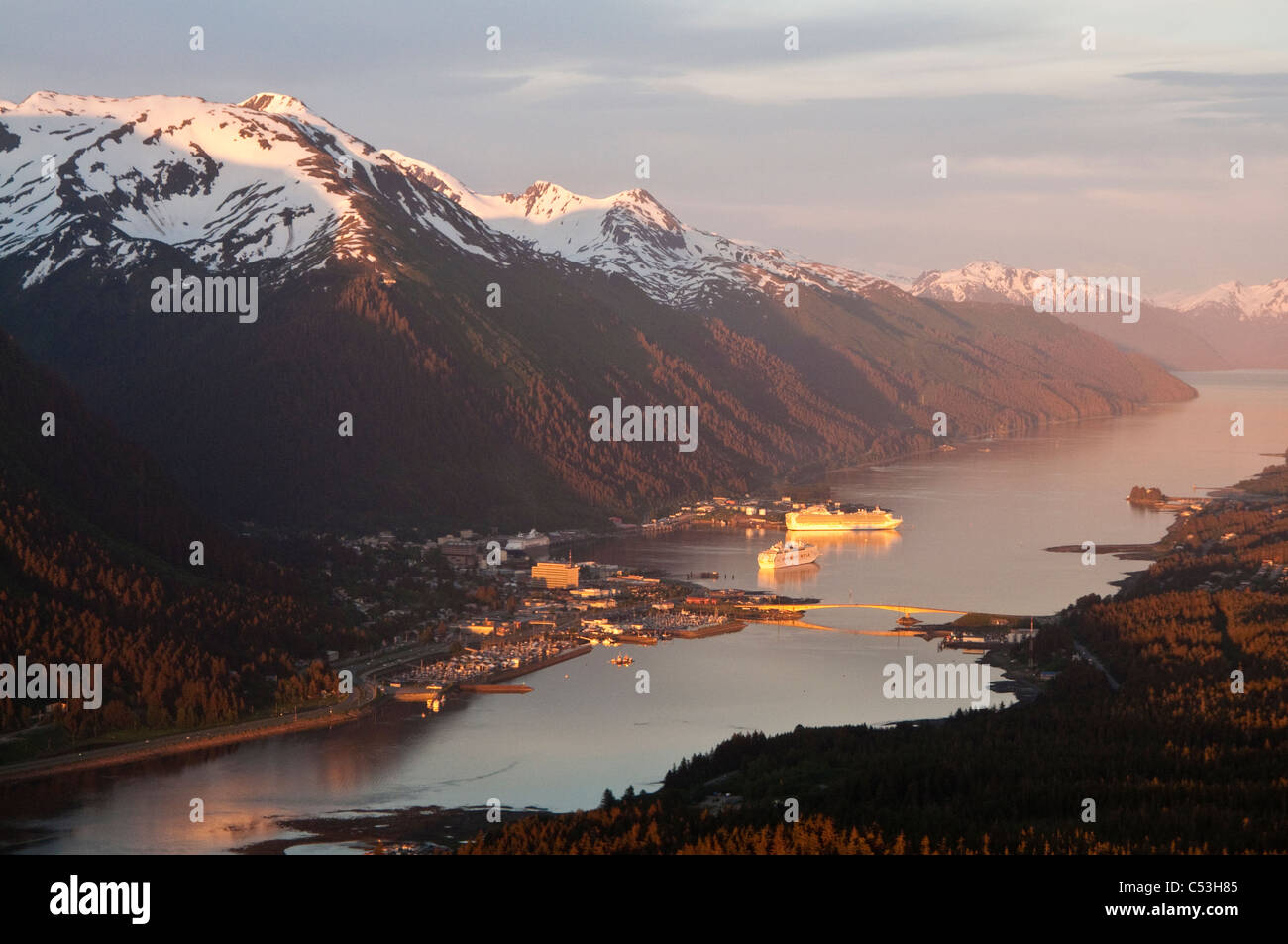 Aerial view of downtown Juneau and harbor at sunset with two cruise ships in port, Southeast Alaska, Summer - Stock Image