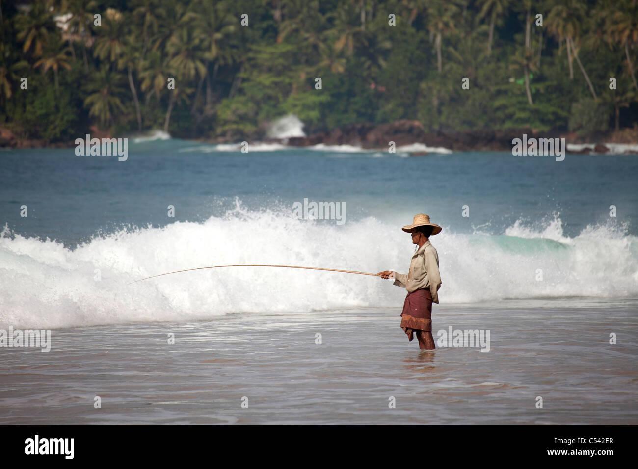fisherman angling in the waves of Mirissa beach, Sri Lanka - Stock Image